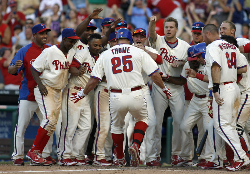 Jim Thome is greeted at the plate after his home run in the bottom of the ninth inning Saturday gave the Phillies a 7-6 victory over the Tampa Bay Rays.