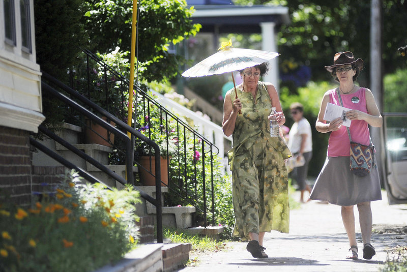 Ann Marie Knoepfel of Portland shades herself with a parasol as she makes her way down Morning Street with Kathleen Egan of South Portland. They were taking part in the Hidden Gardens of Munjoy Hill Tour on Sunday in Portland.