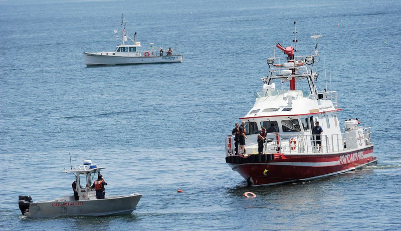 The Portland Fire Boat and other boats converge at the spot where a small plane plunged into Casco Bay on Sunday. Passing boaters pulled a man from the water, but he died.