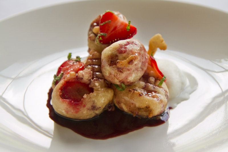 Chef Carmen Gonzales is celebrating the season with a dessert of strawberry and banana fritters, above, served with vanilla bean ice cream and a red wine sauce. Local farmers say the crop is peaking early.