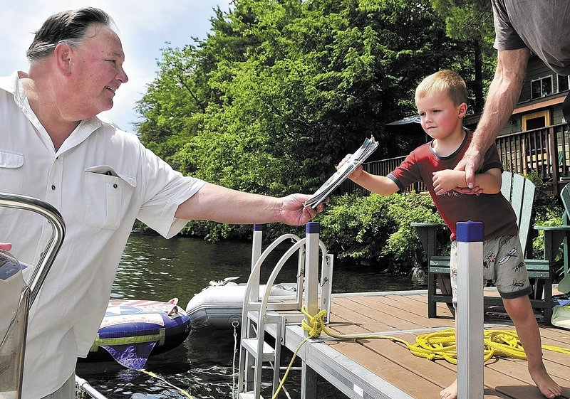 Norman Shaw hands some mail to Canon Smith while making deliveries from his boat Thursday in Belgrade.