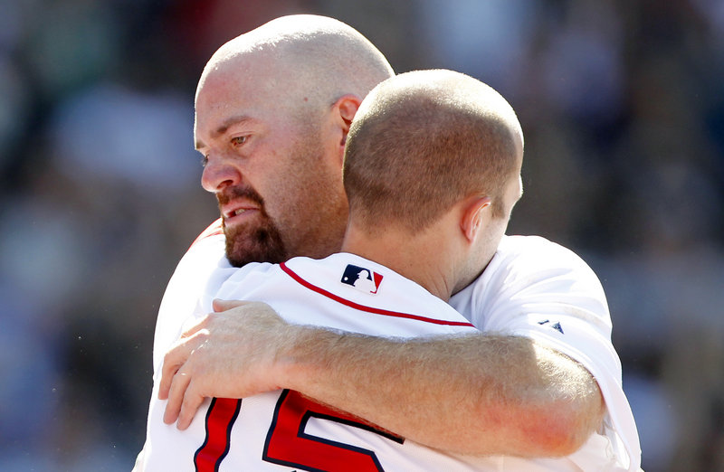 Kevin Youkilis embraces Dustin Pedroia as he leaves Sunday's game against the Atlanta Braves. The Red Sox announced after the game that Youkilis had been traded to the White Sox.