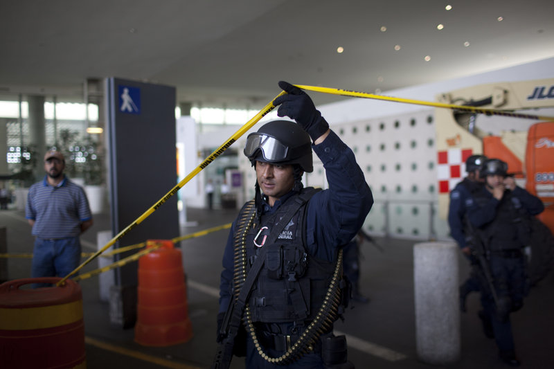 A federal police officer lifts a strip of crime scene tape as he leaves a marked-off area at Mexico City's international airport, where three police officers were killed Monday.