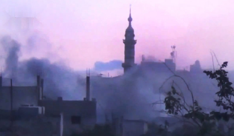 In this image made from amateur video released by the Shaam News Network and accessed Monday, smoke rises from buildings following purported shelling in Homs, Syria. On Monday, the Red Cross said hundreds of civilians are trapped in Homs and aid workers cannot reach them.