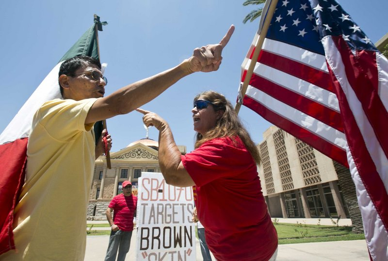 Andy Hernandez, carrying a Mexican flag, and Allison Culver, carrying an American flag, argue over Arizona's immigration law outside the State Capitol in Phoenix on Monday. While finding parts of the Arizona law unconstitutional, the U.S. Supreme Court allowed the law's most-discussed provision to stand.