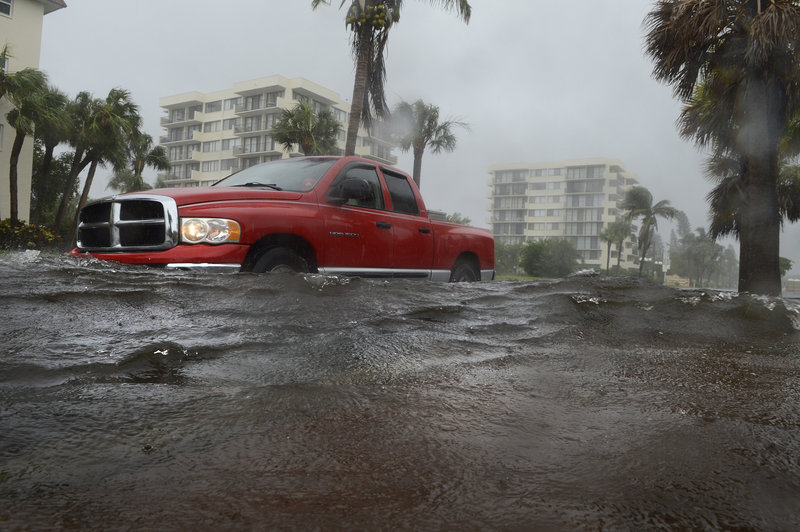 A motorist drives through a flooded road near Siesta Key Public Beach on Monday after rain from Tropical Storm Debby filled streets with water on the Sarasota, Fla., barrier island.