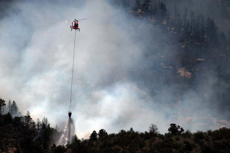 A firefighting helicopter makes a drop on the Waldo Canyon fire west of Colorado Springs, Colo., on Monday.