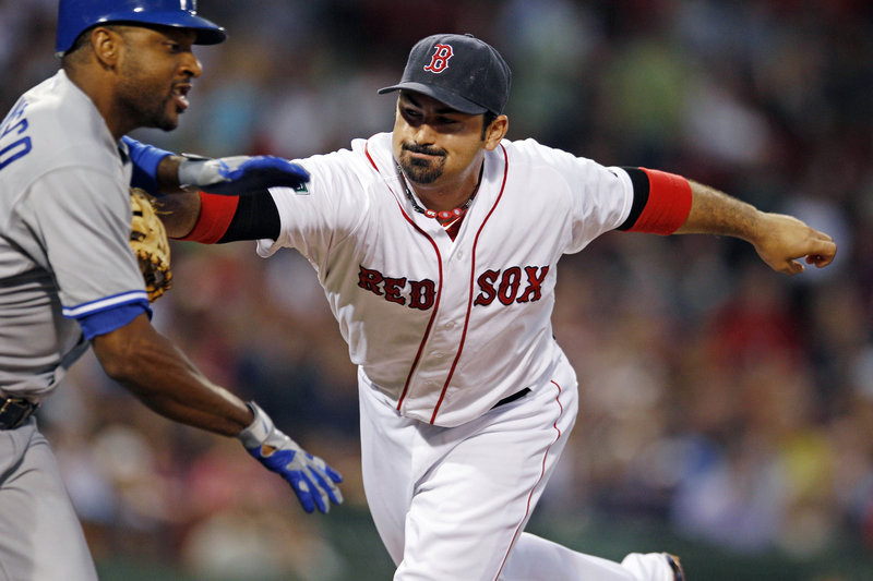 Adrian Gonzalez tags out Toronto's Ben Francisco after a ground ball to first base Monday at Fenway Park. The Red Sox lost, 9-6, in a game delayed by rain for nearly two hours.