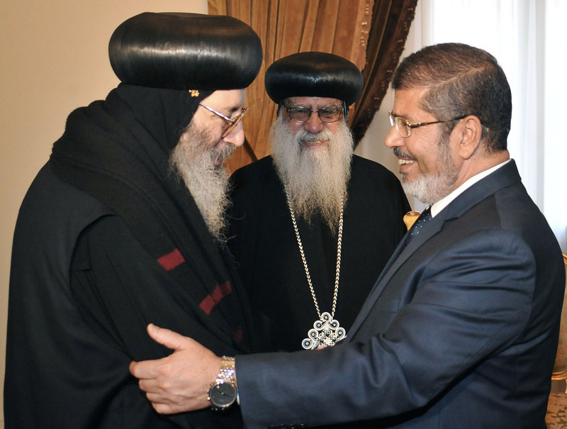 In this photo released by Egypt's official news agency, President-elect Mohammed Morsi shakes hands with a representative from the Coptic community in Cairo on Tuesday. On Sunday, Morsi of the Muslim Brotherhood was declared Egypt's first freely elected president in modern history.