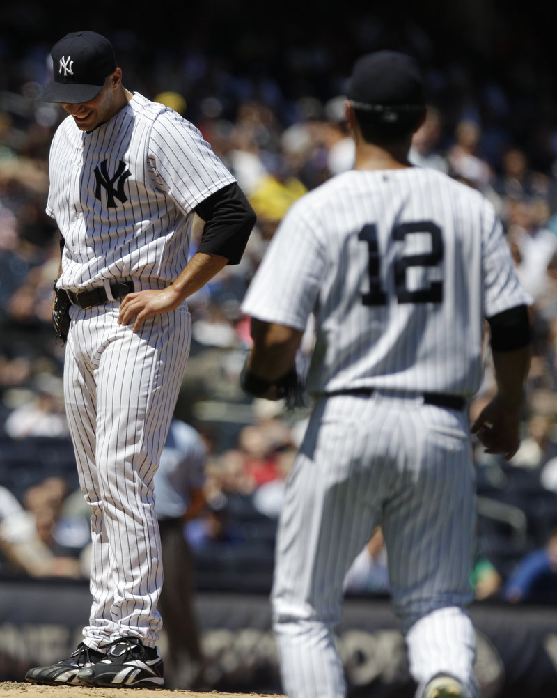 Andy Pettitte of the Yankees grimaces after taking a line drive that broke his left ankle Wednesday as first baseman Eric Chavez approaches. Pettitte may miss at least six weeks.