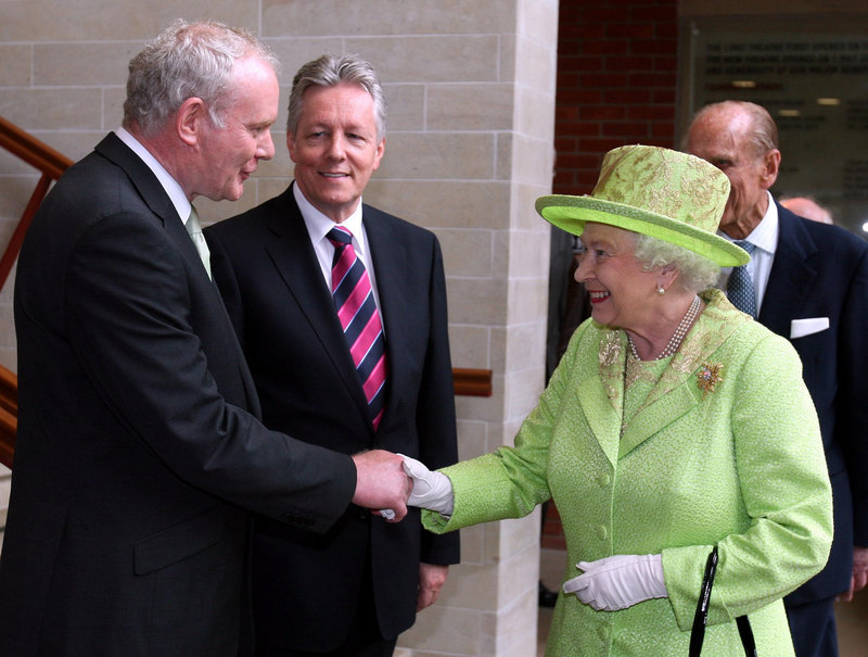 Queen Elizabeth II shakes hands with Northern Ireland Deputy First Minister Martin McGuinness, as First Minister Peter Robinson looks on, Wednesday in Belfast.