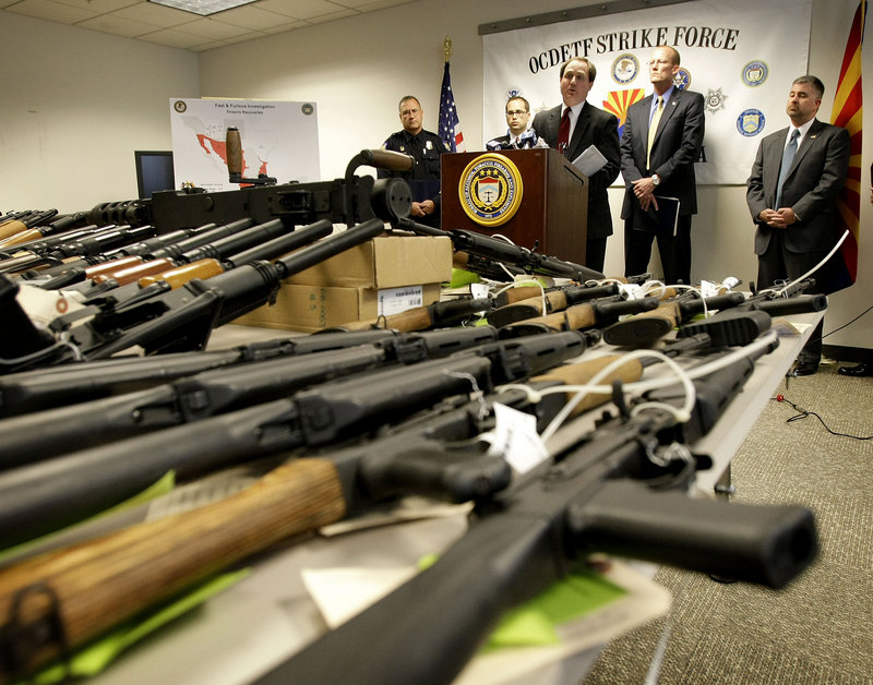 """U.S. Attorney for Phoenix Dennis Burke speaks behind seized weapons in Phoenix last year. Burke was forced to resign amid the fallout from the Justice Department's controversial """"Fast and Furious"""" campaign to rein in gunrunning to Mexican drug cartels."""