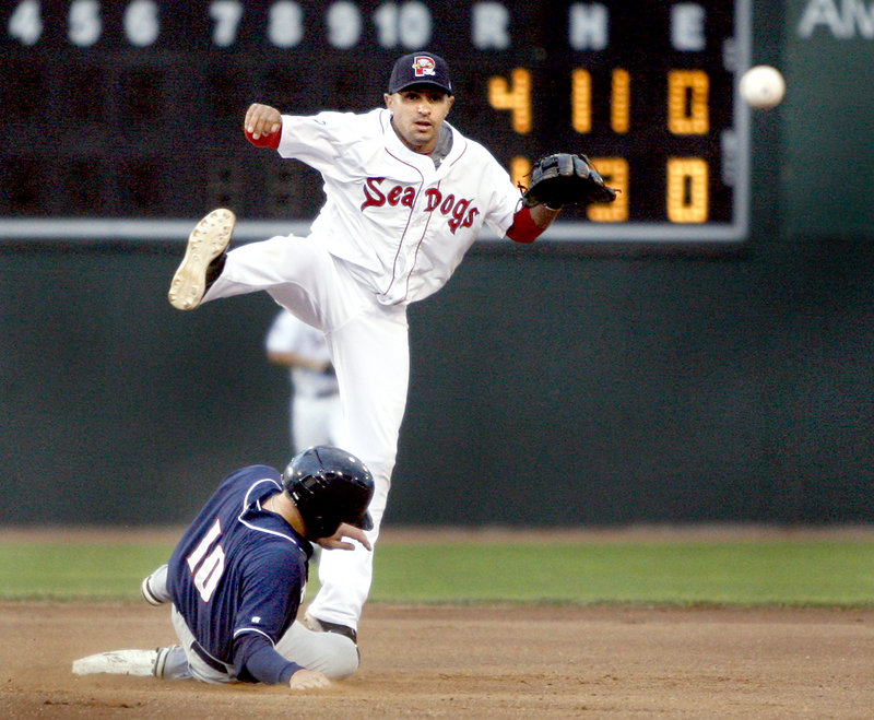 Ryan Dent of the Portland Sea Dogs avoids a slide by Brian Bocock of the New Hampshire Fisher Cats while turning a double play Wednesday night in the fourth inning of New Hampshire's 6-3 victory at Hadlock Field.
