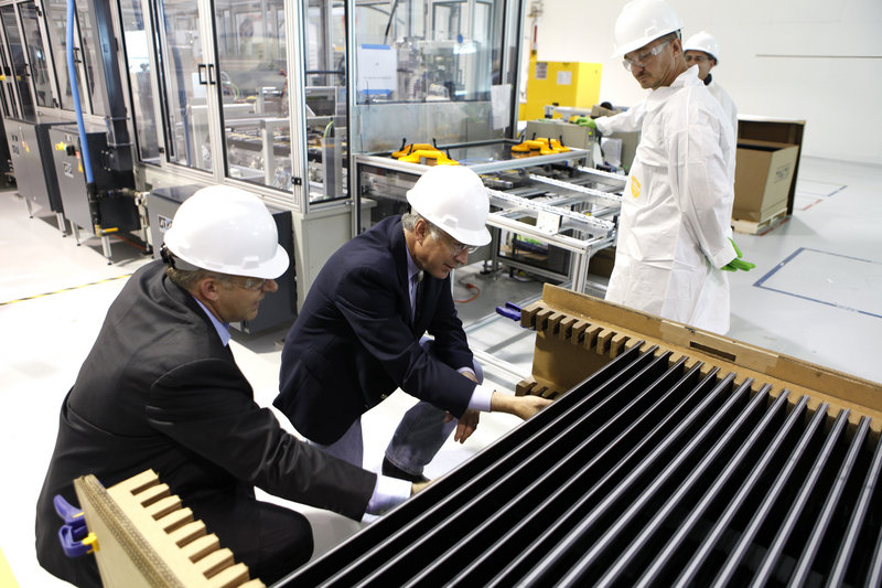 Secretary of the Interior Ken Salazar, right, examines solar electric panels at the Abound Solar manufacturing plant in Longmont, Colo., in 2009.