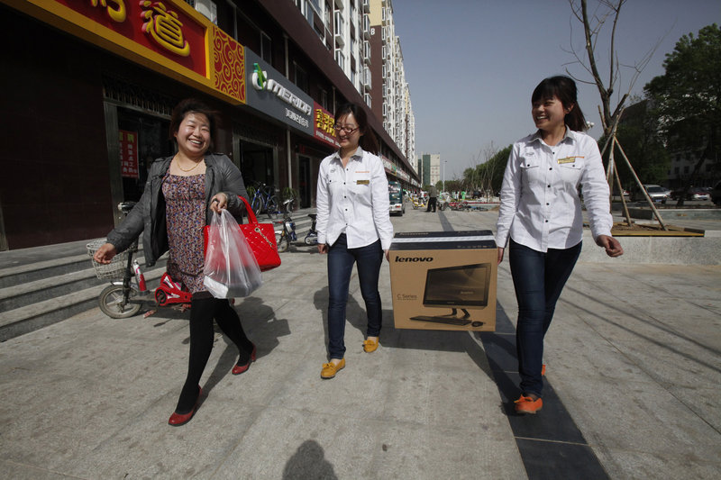 Two Lenovo sales associates carry a newly purchased white Lenovo All-in-One PC for Hou Yan Nan, 26, left, after she bought the computer in Da Shan, China.