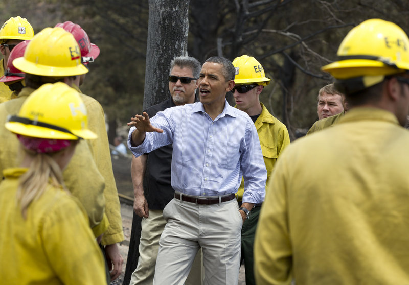 "President Obama talks with firefighters on Friday in a neighborhood of Colorado Springs, Colo. ""The country is grateful for your work. The country's got your back,"" he said."