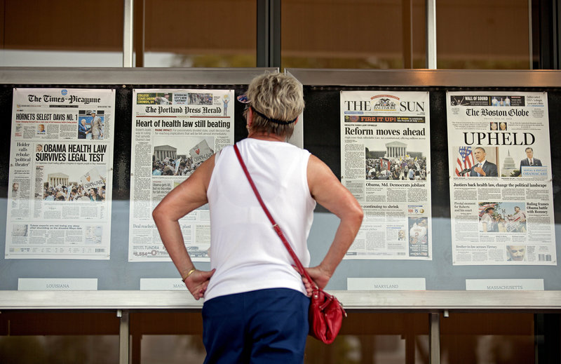 At the Newseum in Washington Friday, a visitor looks at a display of how newspapers from around the country, including The Portland Press Herald, presented the Supreme Court's decision.