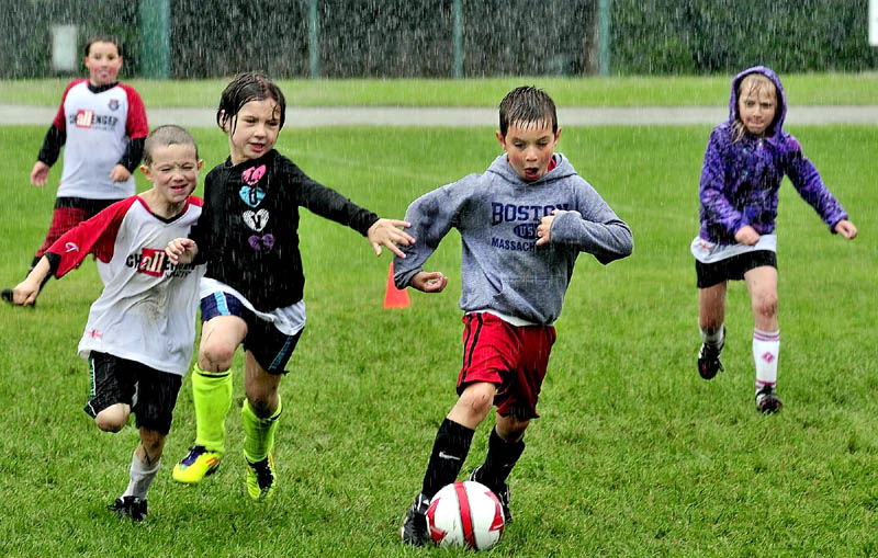 The pouring rain did not stop these kids including Luke Carey as he breaks free with ball during practice in the Challenger Sports soccer program at Carrabec High School on Tuesday.