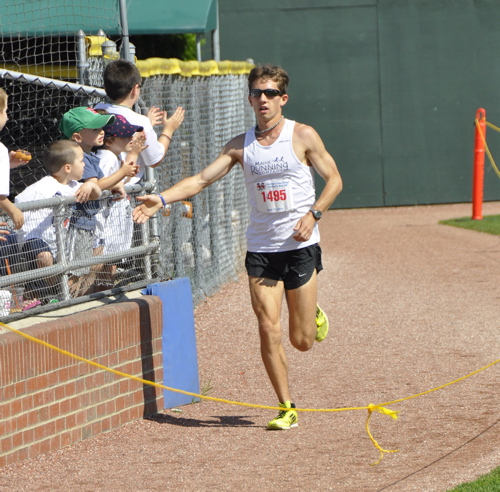 Jonny Wilson of Freeport is greeted by spectators as he approaches the finish line to win the Portland Sea Dogs Father's Day 5K at Hadlock Field.