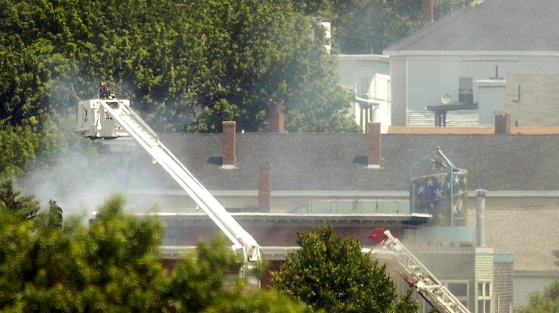 A Portland firefighter lowers a basket closer to the roof of a fire on Montgomery Street in Portland on Monday, July 2, 2012.