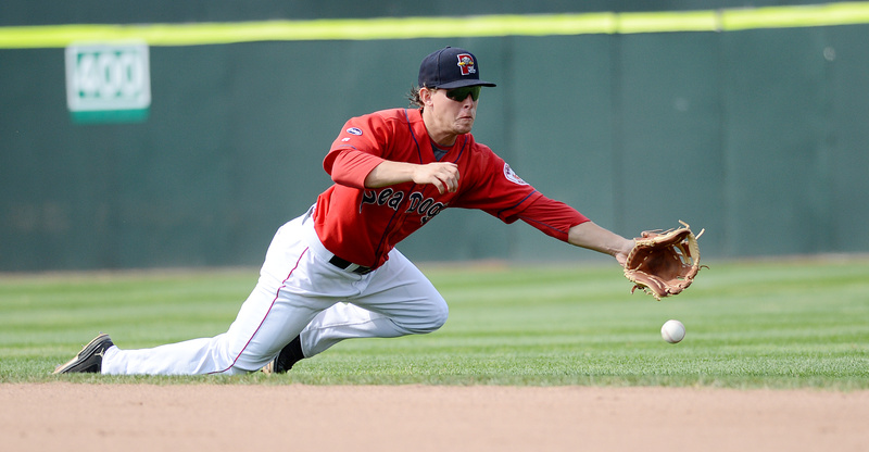 Zach Gentile of the Sea Dogs reaches for a hard-hit grounder in Sunday's game at Hadlock Field. The ball went through to the outfield for a New Hampshire hit.