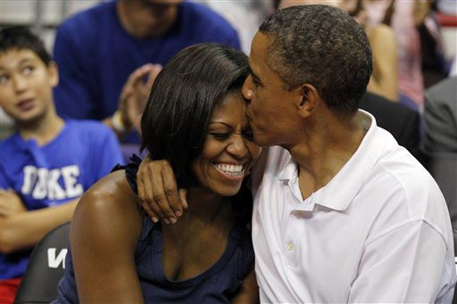 """President Barack Obama kisses first lady Michelle Obama after kissing her for """"Kiss Cam"""" in the second half while attending the Olympic men's exhibition basketball game between Team USA and Brazil on Monday."""