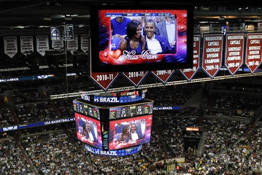 """President Barack Obama and first lady Michelle Obama are seen on the in-house television monitors during the ''Kiss Cam"""" segment as they attend the U.S. men's Olympic basketball exhibition game between Team USA and Brazil in Washington on Monday."""