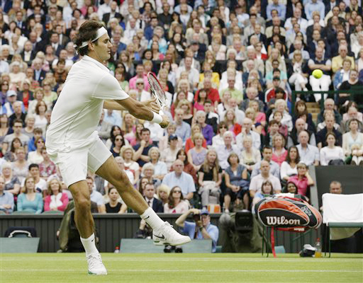 Roger Federer of Switzerland plays a shot to Novak Djokovic of Serbia during a semifinals match at the All England Lawn Tennis Championships at Wimbledon, England, today.