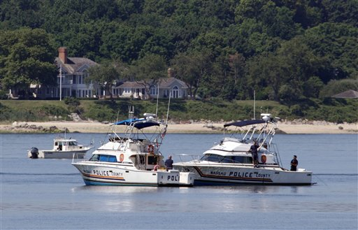 Two Nassau County police boats are stationed near the opening to the Long Island Sound in Lloyd Harbor, N.Y., today. Investigators are trying to learn more about the crucial seconds before a yacht capsized off Long Island, killing three children and leaving 24 others scrambling for their lives. Efforts to raise the boat might begin as early as Friday. (AP Photo/Richard Drew)