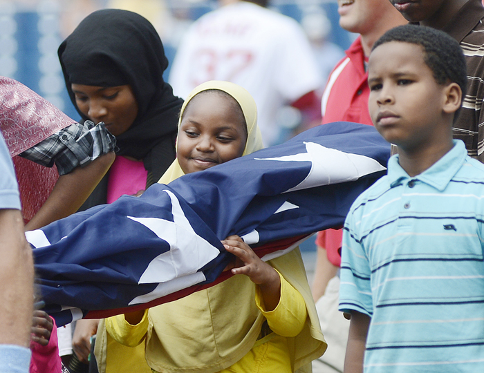 Samira Hassan, 8, of Auburn smiles as she carries the American flag on Hadlock Field for the singing of the national anthem prior to the start of the Portland Sea Dogs game today.