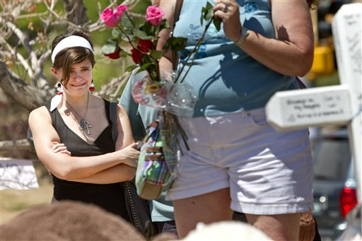 Madison Sherock, 18, becomes emotional while remembering her friend Alex Teves from the Human X Academy, at a makeshift memorial on Monday, across the street from the Century Theater where the mass shooting occurred last Friday killing 12 and injuring dozens of others, in Aurora, Colo. Teves was killed in the attack.