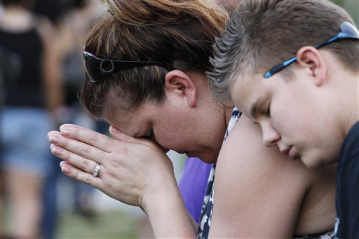 Dylan Bowen, 13, right, holds onto his mother Lorri Hastings as they pray on Sunday, in Aurora, Colo., during a prayer vigil for the victims of Friday's mass shooting at a movie theater.