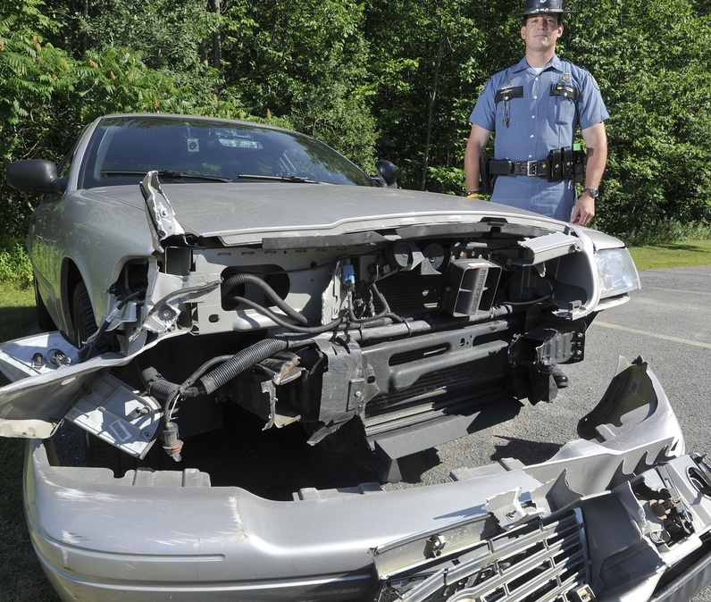 Maine State Police trooper Douglas Cropper stands beside his police car that was damaged while stopping a wrong way driver on I-295.