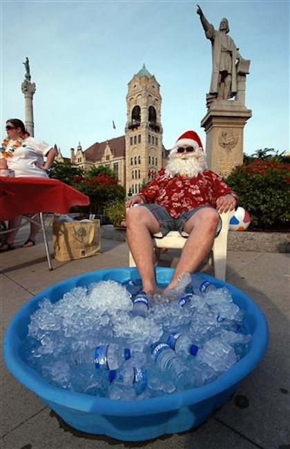 Summer Santa Claus Tom Osborn of Taylor, Pa. a member of the Greater Scranton Jaycees, cools his feet in a pool of ice at Lackawanna County Courthouse Square during First Night festivities held in downtown Scranton, Pennsylvania on Friday, July 6, 2012. (AP Photo/The Scranton Times-Tribune, Butch Comegys)