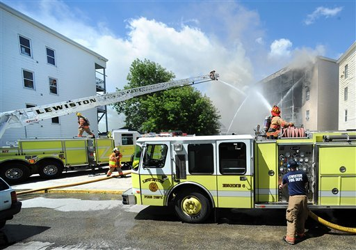 Lewiston and surrounding area fire departments battle a fire on Tuesday involving a 12-unit four-story apartment building, a one-and-a-half story single-family structure next door and a third building adjacent to it.