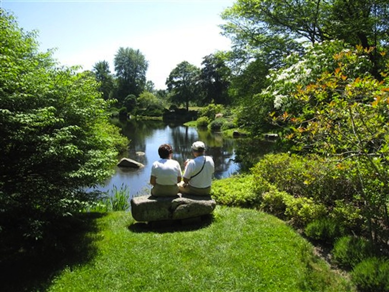 In this July 12, 2012 photo, visitors sit on a rock bench to view the scenery at the Asticou Azalea Garden pond in Northeast Harbor, Maine. The garden includes plants from the collection of renowned landscape designer Beatrix Farrand, who has connections to several gardens in the area, including the nearby Abby Aldrich Rockefeller Garden, a private garden thatís only open to the public a few days a year. (AP Photo/Beth J. Harpaz)
