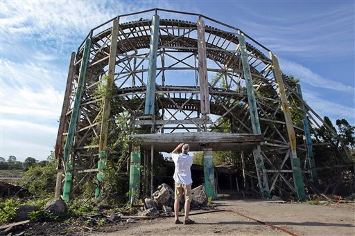 Chuck Damore, who was a regular at Lincoln Park during his youth, takes a photo of some remains of the Comet roller coaster at the defunct amusement park in Dartmouth, Mass., Wednesday July 11, 2012. Demolition crews on Wednesday started tearing down the crumbling roller coaster to clear the site for a development that will include single-family homes, apartments and commercial space. (AP Photo/The Standard-Times, Peter Pereira) entertainment;coaster;roller coaster;wooden;fun;demolition