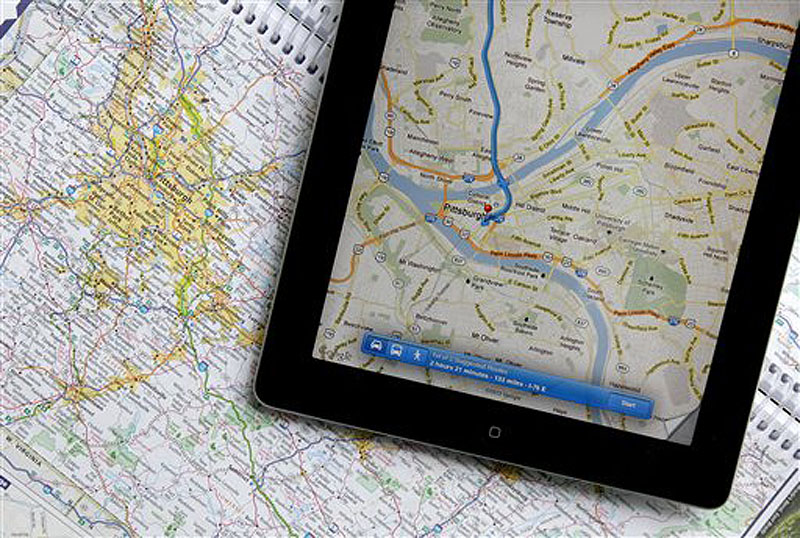 In this Tuesday, May 8, 2012 photo a traditional road map of the Pittsburgh area and one showing the same region on an iPad are seen placed together in Moreland Hills, Ohio. Transportation agencies around the country are printing fewer maps to cut costs or just to acknowledge that public demand is down. (AP Photo/Amy Sancetta)