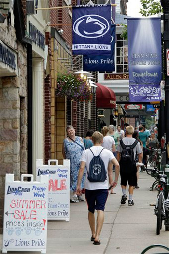 People walk past the shops on College Avenue in the heart of downtown State College, Pa, home of the Pennsylvania State University on Monday, July 23, 2012. State Farm is pulling its ads from broadcasts of Penn State football games, while General Motors is reconsidering its sponsorship deal. (AP Photo/Gene J. Puskar) NCAA