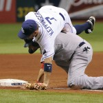 Boston's Cody Ross gets out from underneath Tampa Bay Rays third baseman Jeff Keppinger before sprinting home to score on a throwing error by Rays pitcher David Price during the sixth inning.
