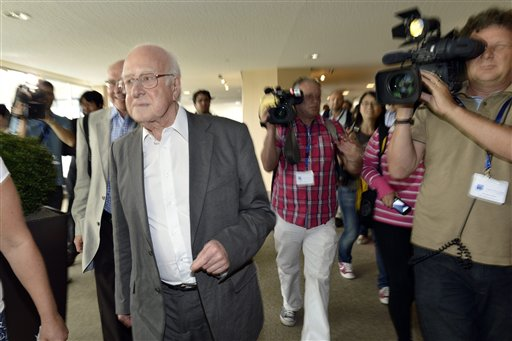 British physicist Peter Higgs, left, arrives to hear about the latest update in the search for the Higgs boson at the European Organization for Nuclear Research (CERN) in Meyrin near Geneva, Switzerland, today.