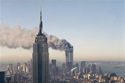 In this Sept. 11, 2001, file photo, the twin towers of the World Trade Center burn behind the Empire State Building in New York. The Sept. 11, 2001 terrorist attack is by far the most memorable moment shared by television viewers during the past 50 years, a study released on Wednesday, July 11, 2012, concluded. (AP Photo/Marty Lederhandler, File) 9/11 attacks building center empire state terrorist trade world xiconicx