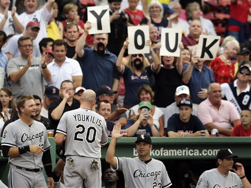 Chicago White Sox third baseman Kevin Youkilis is congratulated by teammates and fans after scoring on a throwing error during the first inning of Monday's game against the Boston Red Sox at Fenway Park.