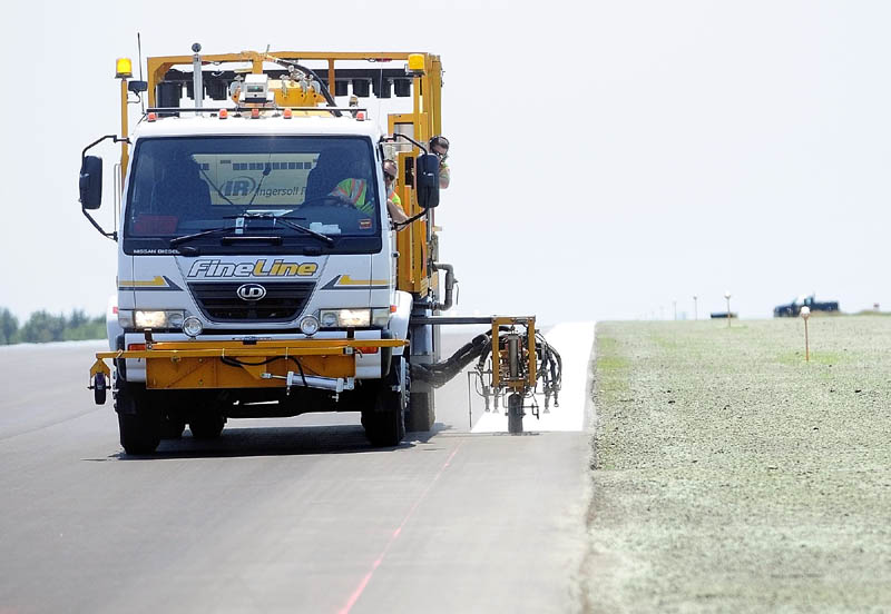 A truck paints a stripe on the edge of the newly repaved runway that reopened at the Augusta State Airport. Part of the project included narrowing the width of the runway, which the newly reseeded lawn on the right side shows.