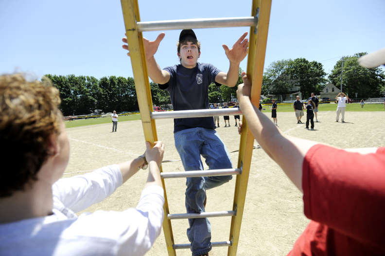 Connor Curran of the Kennebunk Fire Department makes his way up a ladder during a competition at the York Beach Fire Department Annual Parade and Muster on Sunday.