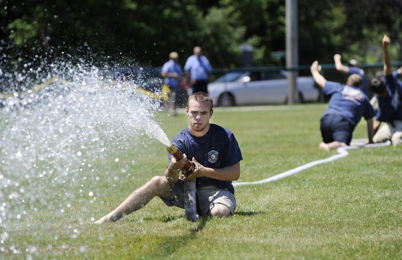Matt Doe of the Kennebunk Fire Department aims his team's hose at a target during the muster in York Beach on Sunday.