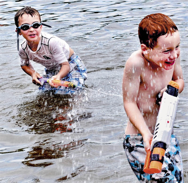 Noah McMahon, left, blasts Camden Herrick with a water gun while cooling off at Lake George Regional Park in Canaan on a hot and humid Friday.