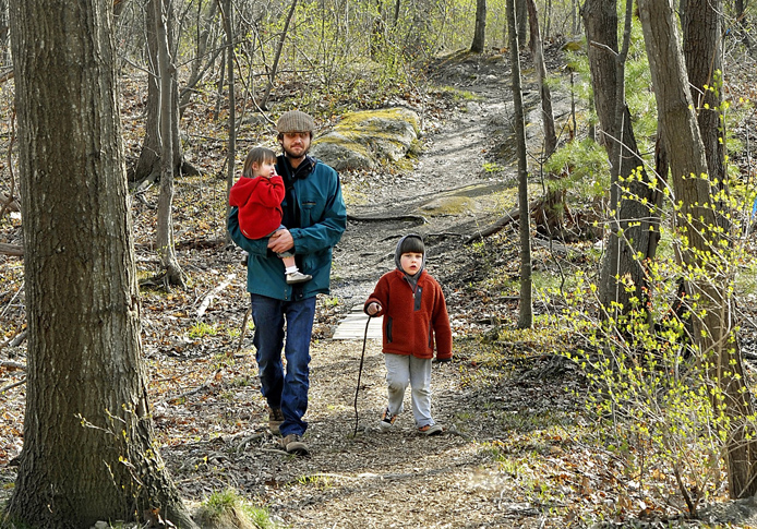 "Back Cove area resident Tim Willoughby enjoys a spring walk in the Canco Woods with his daughter, Maeve, 2, and son Thomas, 4. Parenting Magazine describes Portland as a great place for ""a laidback lifestyle that encourages healthy, active family living."""