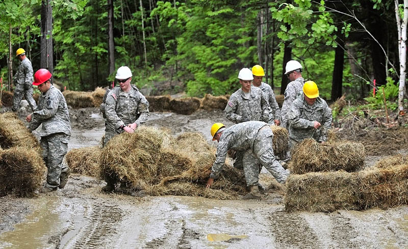 Maine Army National Guard soldiers stack haybales into a check dam to prevent erosion on a road they built during a summer training project at the Augusta Trails complex last week in Augusta. The 2nd Platoon of the 262 Engineer Company built a section of the road in the complex that is located between the Augusta State Airport and Bond Brook Road.