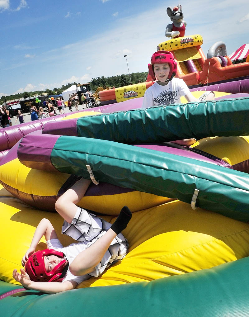 Dylan Perry, left, and Isaiah McCarthy, both 10 of Augusta, battle in the inflatable jousting pit during Saturday's Whatever Family Festival Kid's Day.